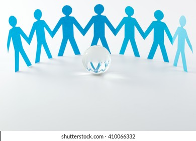 Cut out of blue paper people form in a semi circle in front of crystal globe