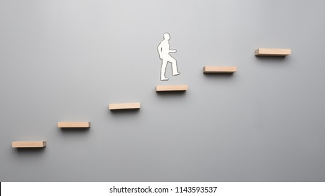 Cut outs of paper man climbing the steps to success in a conceptual image over gray background.