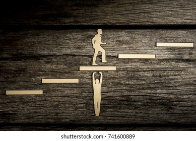 Cut outs of paper men with one supporting steps and the other one climbing the steps in a conceptual partnership image.