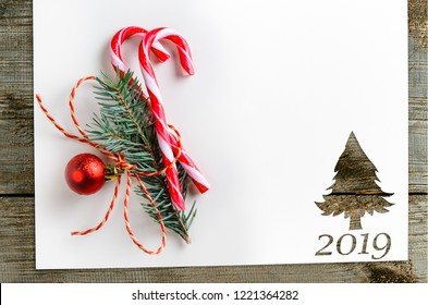 Cut paper in fir-tree shape for 2019 christmas card or new year background on wooden table