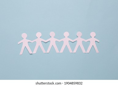 Cut paper human chain hold hands and show their unity on blue background. Solidarity and peace