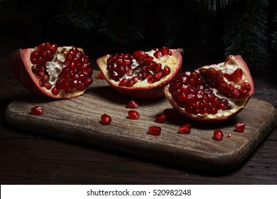 cut part of pomegranate on a wooden board on a wooden background on the background of trees. New Year's holiday. tree branch