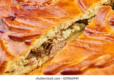 Cut pie with chicken and mushrooms on a wooden table