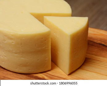 Cut a piece of cheese triangular shape from a large cheese head. On a wooden surface, close-up