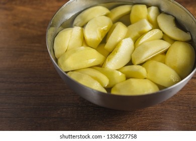 Cut pieces of apple in a bowl with water on wooden table top.