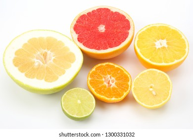 cut pieces of different citrus fruits on white background