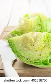 Cut pieces of iceberg lettuce with kitchen knife on cutting board.