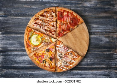 Cut pieces of pizza with different flavors, without one piece, on a wooden table.