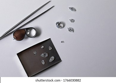 Cut and polished diamonds with loupe, tweezers, scoop on white and blue background. Gemstones demonstration.