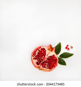 Cut pomegranate with green leaves and juicy pomegranate seeds on a white background - Shutterstock ID 2044173485