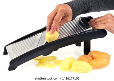 Cut potatoes with a kitchen mandolin on a white background - Shutterstock ID 1416179108