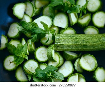 Cut raw courgettes in a frying pen ready to be cooked with mint as pasta sauce