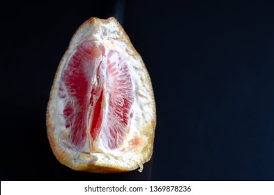 Cut in red grapefruit isolated on black background. Red grapefruit looking like female vagina, vulva symbol