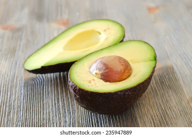 Cut ripe black  Avocado on wooden background