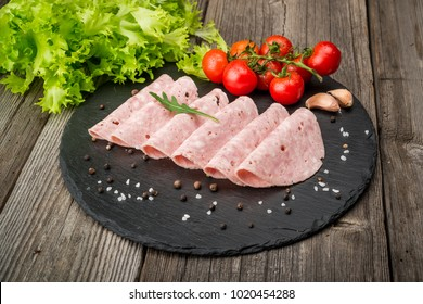 Cut sausage from ham on a wooden background. With spices