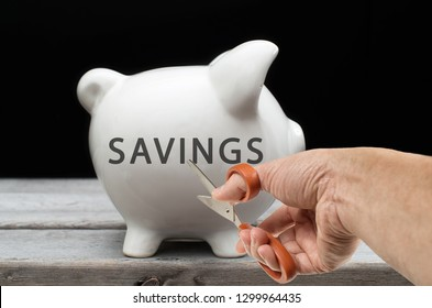 Cut savings concept with hand holding scissors towards a piggy bank