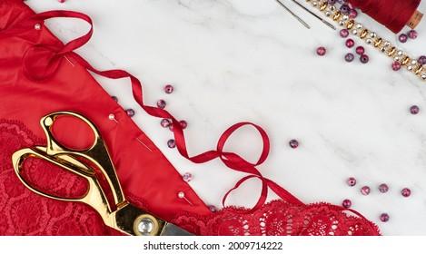Cut and sew customized garments. Gold scissors, threads, fabrics on a marble table. Sewing feminine, festive, glamorous, evening, wedding dresses, bridesmaids dress.