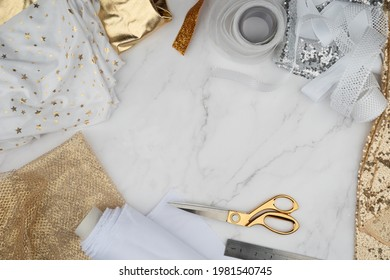 Cut and sew customized garments, sewing accessories. Gold scissors, threads, fabrics, marble table. Sewing feminine, festive, glamorous, evening, wedding dresses, bridesmaids dress. Empty copy space