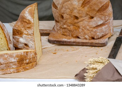 Cut slices of freshly baked loaf of traditional rustic bread on cutting board and bunch of wheat ears wrapped in paper
