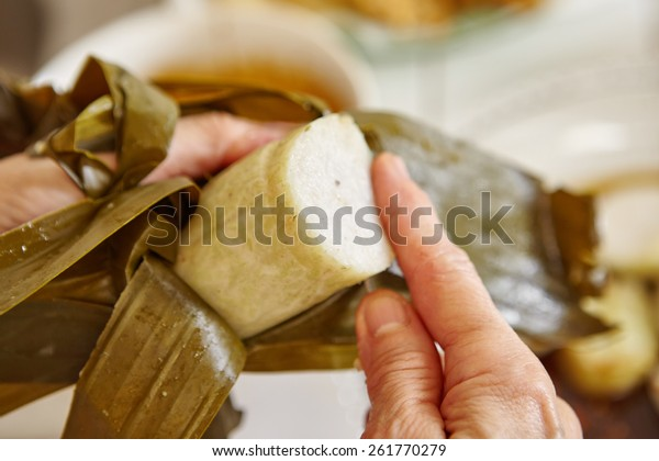 """Cut the steamed rice cake (""""lontong"""" in Indonesian) wrapped in banana leaf"""