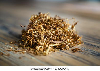Cut tobacco leaves on the wooden background