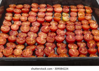 cut tomatoes in half laid on a baking sheet
