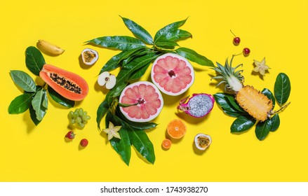 Cut in two halves grapefruit with different exotic tropical fruits and green leaves on bright yellow background. Raw eating diet concept. Super natural food