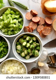 Cut vegetables and andouille sausage for gumbo,  top view, on a white granite surface