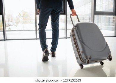 Cut view of businessman in suit walking in hall. He rolls his suitcase behind. Guy wait for flight.
