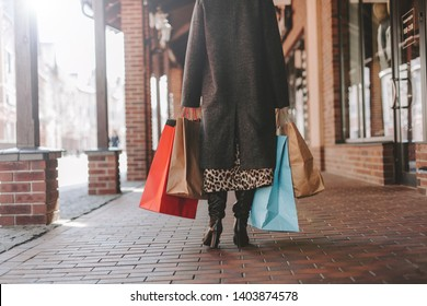 Cut view of fasionable model in coat shopping in mall. Walking alone. Colorful bags in both hands. Sun shining. Beautiful daylight outside