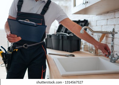 Cut view of handyman holding tool box and wrench in hands. He stand in kitchen at sink. He open water tap.