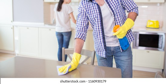 Cut view of man cleaning the surface of wood table. He wears yellow gloves. Guy uses blue rag for cleaning. His wife is doing the same thing further forward.