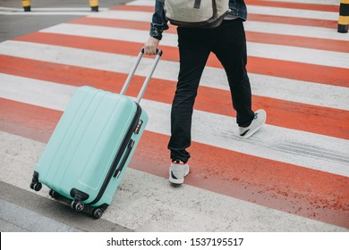 Cut view of man walking on crosswalk and carrying blue suitcase. Also having backpack on back. Going on vacation or travelling abroad. Small of big trip