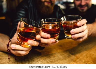 Cut view of three bearded young men holding glasses with rum together. They smile. People sit in bar.