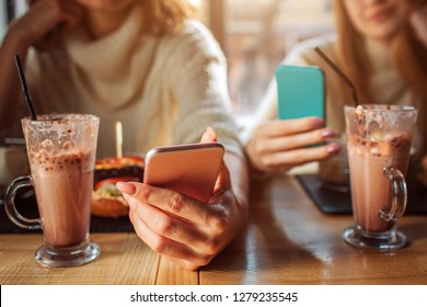 Cut view of two young women hold phones in hands. The look at it. Younf women sit inside at table. Glasses with chocolate cocktais are on table.