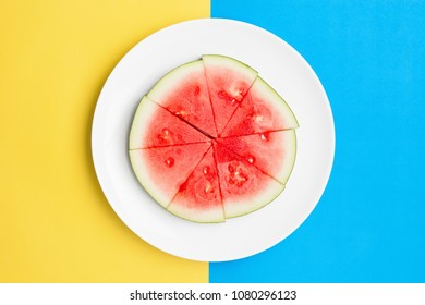 Cut watermelon on round plate with contrasting split color background.