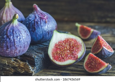 Cut and whole figs on dark, wooden background