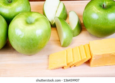 Cut and whole green granny smith apples with cheddar cheese