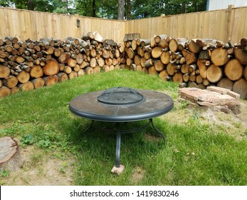 cut wood stacked along brown wooden fence and fire pit