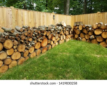 cut wood stacked along brown wooden fence