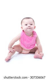 A cute 1 year old girl wearing a pink bib sitting on white.