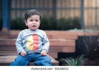 Cute 1 year old mixed race Asian Caucasian boy sits and cries in his landscaped garden backyard. Cross processed cool tones