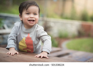 Cute 1 year old mixed race Asian Caucasian boy plays happily in his landscaped garden backyard