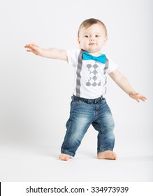 a cute 1 year old stands in a white studio setting. The boy looks as if he is surfing in the studio.. He is dressed in t-shirt, jeans, suspenders and blue bow tie