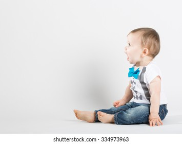 a cute 1 year old stands in a white studio setting. The boy is yelling with an open mouth. He is dressed in t-shirt, jeans, suspenders and blue bow tie