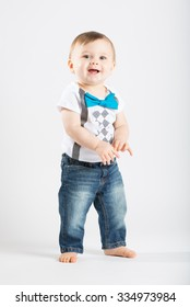 a cute 1 year old stands in a white studio setting. The boy has a happy expression. He is dressed in t-shirt, jeans, suspenders and blue bow tie