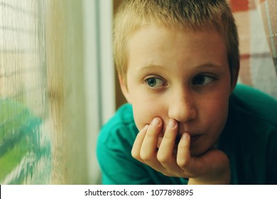 Cute 10 year old autistic boy looking at the rain