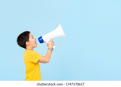 Cute 10 year old  boy shouting on megaphone isolated on light blue background with copy space