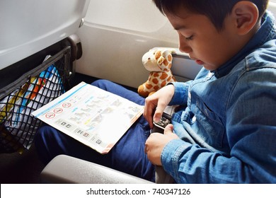 cute 10 years old asian kid boy fasten seat belt with airplane onboard safety information suggestion card on his lap and giraffe plush toy and copy space , safety travel with kid concept