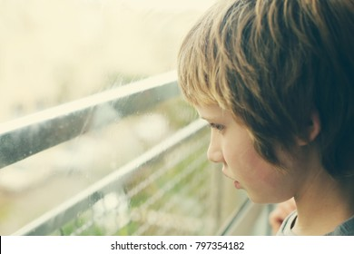 Cute 10 years old autistic boy looking through the window